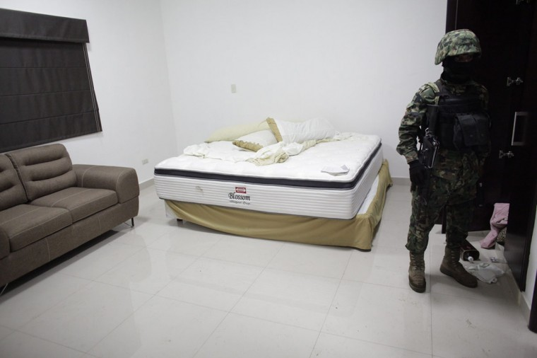 "A Mexican Marine stands in the bedroom of one of the houses of Mexican kingpin Joaquin ""Chapo"" Guzman during a presentation for the media in Culiacan February 27, 2014. Guzman, who rose from humble origins to become one of the most powerful drug barons in history, was captured on Friday in Sinaloa. (REUTERS/Daniel Becerril)"