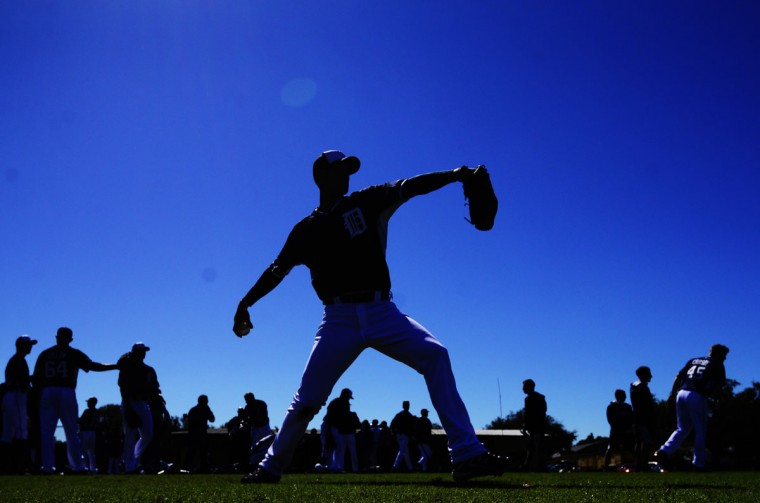 Detroit Tigers starting pitcher Rick Porcello (21) is silhouetted as he throws during the Detroit Tiger's first workout of Spring Training at Joker Marchant Stadium. (David Manning-USA TODAY Sports)