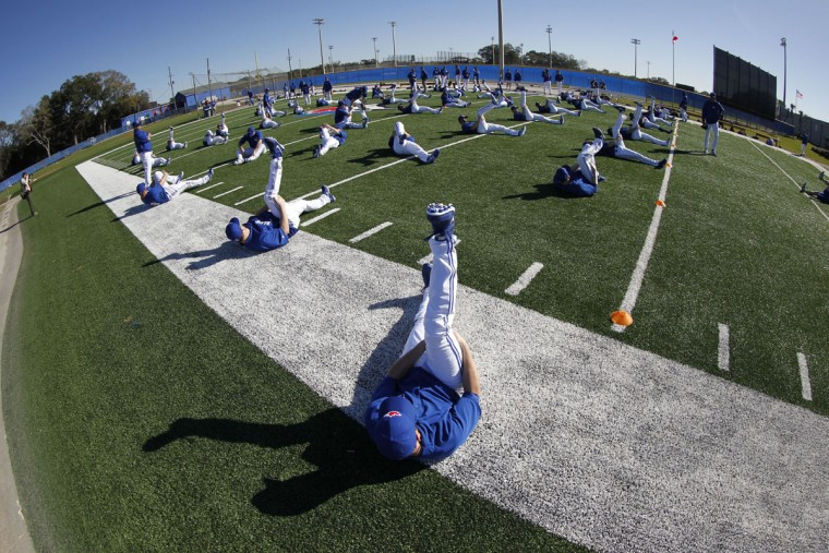 Toronto Blue Jays catcher Josh Thole (22) and teammates stretch before they workout for spring training at Bobby Mattick Training Center . (Kim Klement-USA TODAY Sports)