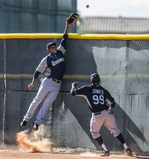 A fly ball is just beyond the reach of Seattle Mariners' Julio Morran during spring training in Peoria, Ariz, on Feb. 22, 2014. (Dean Rutz/Seattle Times/MCT)