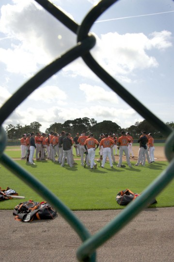 Baltimore Orioles position players encircle manager Buck Showalter who discusses defensive fielding drills. (Karl Merton Ferron/Baltimore Sun Staff)