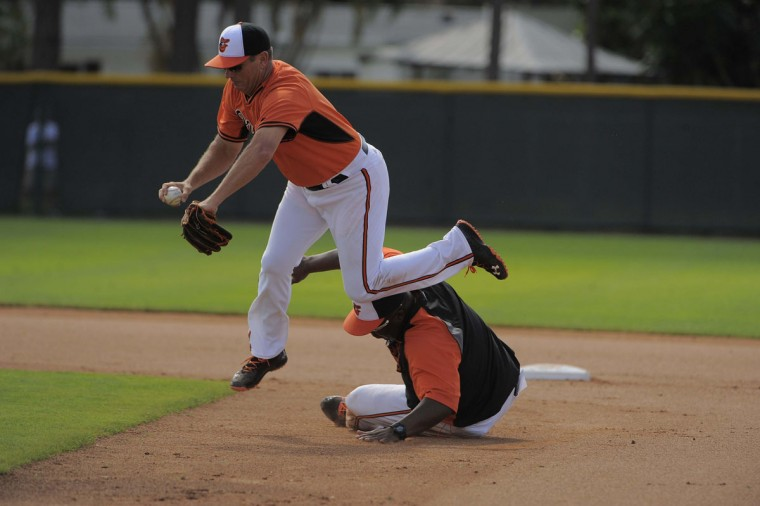Baltimore Orioles coach Bobby Dickerson tumbles above coach Wayne Kirby (below) who slides to demonstrate potential base running scenarios. (Karl Merton Ferron/Baltimore Sun Staff)