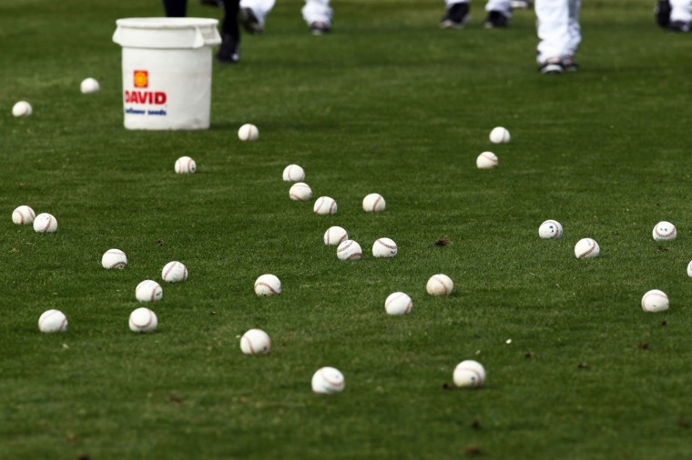 Milwaukee Brewers prepare to pick up dozens of base balls used in Spring Training practice at Maryvale Baseball Park. (Lance Iversen-USA TODAY Sports)