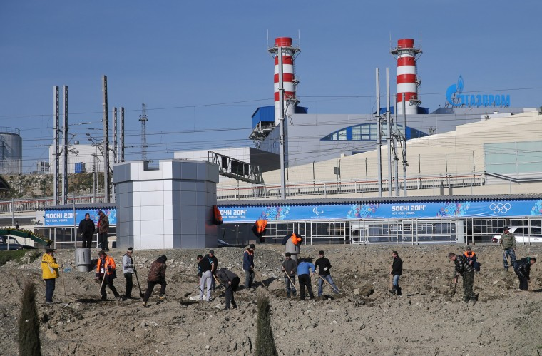 Landscapers work near the Olympic Park train stop hours in Sochi, Russia hours before the opening ceremonies of the Winter Olympics, Friday, Feb. 7, 2014. (Brian Cassella/Chicago Tribune/MCT)