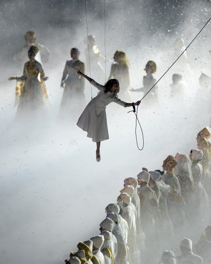 """Lubov"" (Love), the main character featured in the Opening Ceremony of the 2014 Winter Olympics, is suspended over performers in classic Russian costumes at Fisht Olympic Stadium in Sochi, Russia, Friday, Feb. 7, 2014. (Chuck Myers/MCT)"