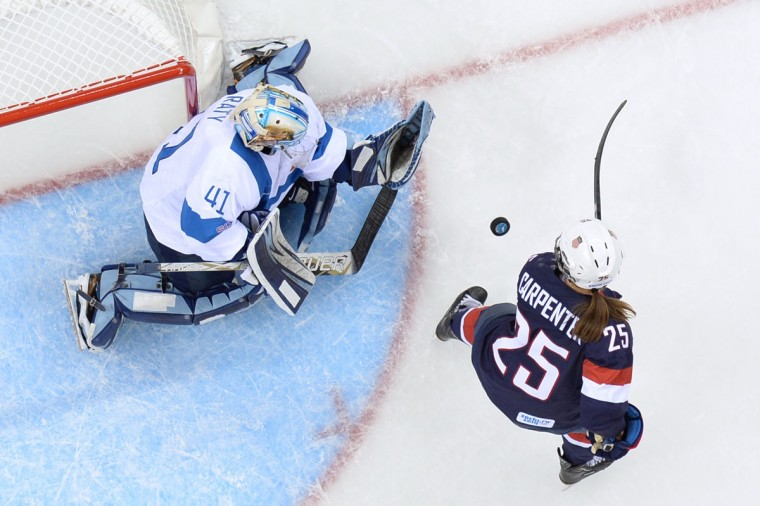 US Alex Carpenter (R) tries to score against Finland's goalkeeper Noora Raty during the Women's Ice Hockey Group A match USA vs Finland at the Shayba Arena against team Finland during the Sochi Winter Olympics on February 8, 2014. (Jonathan Nackstrand/AFP/Getty Images)