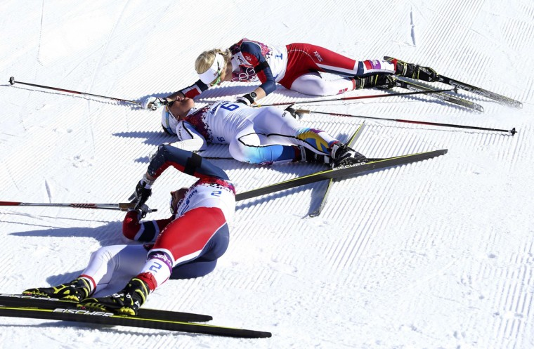 First placed Marit Bjoergen (bottom) of Norway, her team mate and fourth placed Therese Johaug (top) and second placed Charlotte Kalla of Sweden react after competing in the women's skiathlon event at the Sochi 2014 Winter Olympics in Rosa Khutor February 8, 2014. (REUTERS/Sergei Karpukhin)