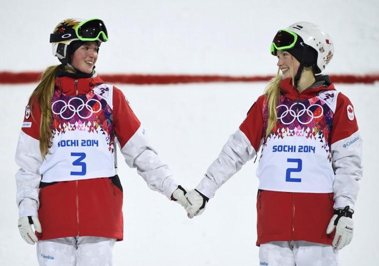 Second-placed Chloe Dufour-Lapointe (L) of Canada and her sister, first-placed Justine Dufour-Lapointe (R), hold hands during the flower ceremony for the women's freestyle skiing moguls event at the Sochi 2014 Winter Olympics in Rosa Khutor, February 8, 2014. (REUTERS/Dylan Martinez)