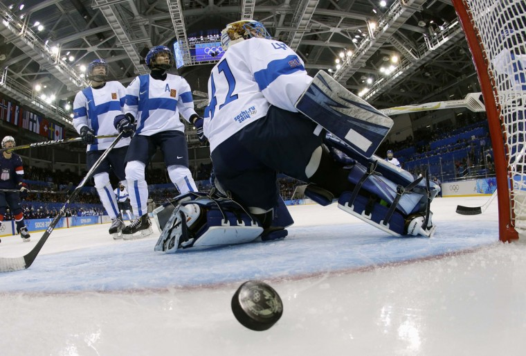 The puck goes into the net behind Finland's goalie Noora Raty for USA's second goal scored by Kelli Stack, during the second period of their women's preliminary round hockey game at the Sochi 2014 Winter Olympic Games February 8, 2014. (REUTERS/Matt Slocum/Poo)