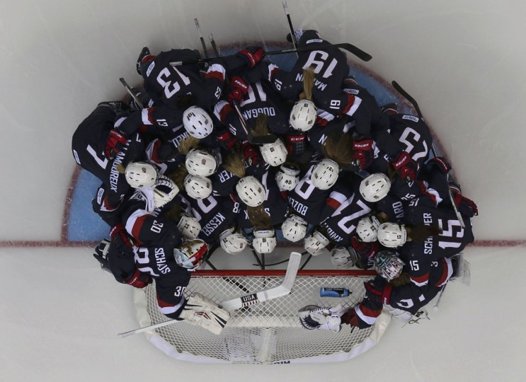 The U.S. women's hockey team huddles around the net before their preliminary round hockey game against Finland at the Sochi 2014 Winter Olympic Games February 8, 2014. (REUTERS/Mark Blinch)