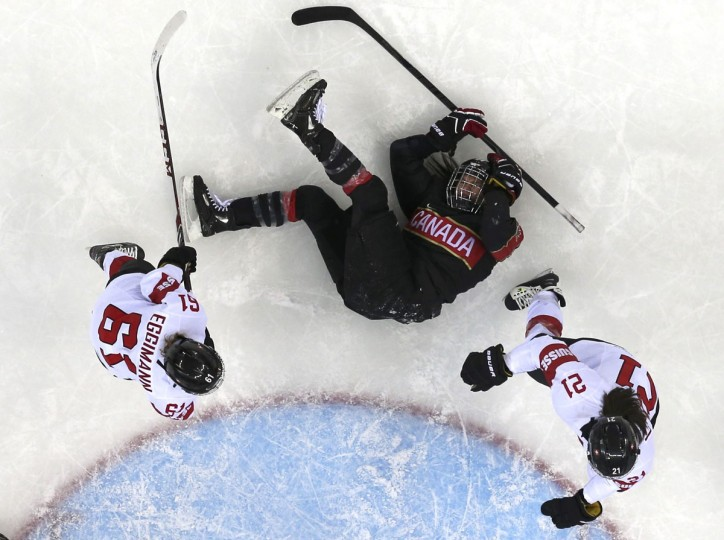 Canada's Natalie Spooner is knocked to the ice by Switzerland's Romy Eggimann (L) and Laura Benz during the second period of their women's ice hockey game at the Sochi 2014 Winter Olympics February 8, 2014. (REUTERS/Mark Blinch)
