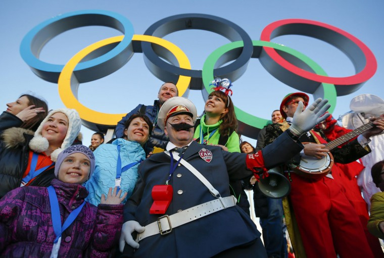 Fans cheer underneath the Olympic rings during the Sochi 2014 Winter Olympics February 8, 2014. (REUTERS/Shamil Zhumatov)