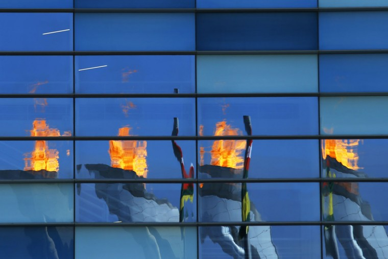 The Olympic flame is reflected in the Iceberg Skating Palace at the Sochi 2014 Winter Olympics February 8, 2014. (REUTERS/Brian Snyder)