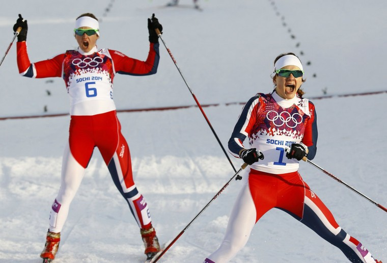 Winner Maiken Caspersen Falla (R) of Norway and her team mate, second placed Ingvild Flugstad Oestberg celebrate after competing in the women's cross-country sprint free final at the Sochi 2014 Winter Olympic Games in Rosa Khutor February 11, 2014. (REUTERS/Kai Pfaffenbach)