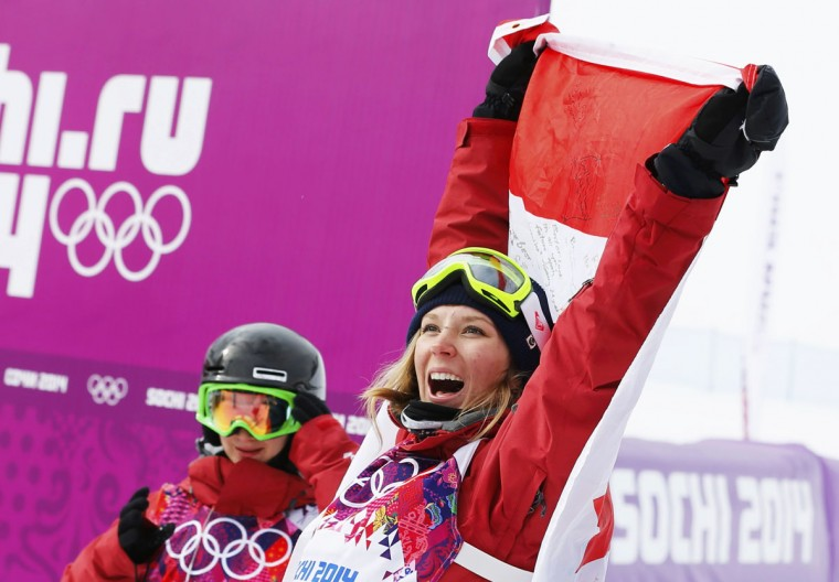 Winner Canada's Dara Howell (R) celebrates with the Canadian flag as compatriot and third-placed Kim Lamarre looks on after the women's freestyle skiing slopestyle finals at the 2014 Sochi Winter Olympic Games in Rosa Khutor February 11, 2014. (REUTERS/Mike Blake)