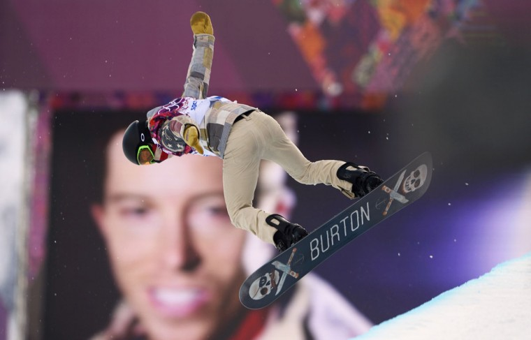 Shaun White of the U.S. performs a jump near a picture of himself during the men's snowboard halfpipe qualification round at the 2014 Sochi Winter Olympic Games in Rosa Khutor February 11, 2014. (REUTERS/Dylan Martinez)
