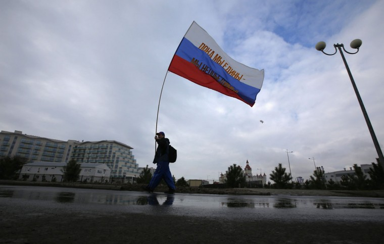 "A fan carries a Russian flag bearing the words ""When we are together we shall win"", near the Olympic Park in Sochi February 11, 2014. (REUTERS/Eric Gaillard)"
