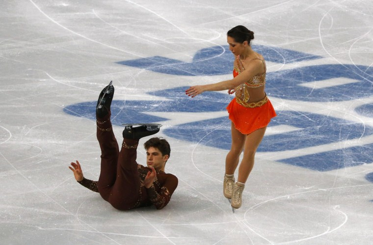 Italy's Nicole Della Monica (R) looks on as her partner Matteo Guarise falls, as they compete during the figure skating pairs short program at the Sochi 2014 Winter Olympics, February 11, 2014. (REUTERS/David Gray)