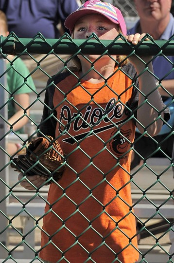 Riley Crowl, 8, of Hampstead, peers over the fence to watch the Orioles participate in drills at the club's spring training facility. (Karl Merton Ferron/Baltimore Sun)