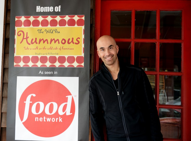 Blake Wollman, owner of Desert Cafe in the Mount Washington Village, poses for a photo next to a sign advertising his Wild Pea Hummous and its recognition on the Food Network. Friday, Jan. 31, 2014. (Jon Sham/BSMG)