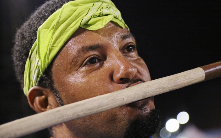 Stick fighter Learie Licorish, of the Campbell Trace gayelle, or stick fighting arena, kisses his stick after beating his rival during the finals of the national stick fighting competition, in San Fernando. (Andrea De Silva/Reuters photo)