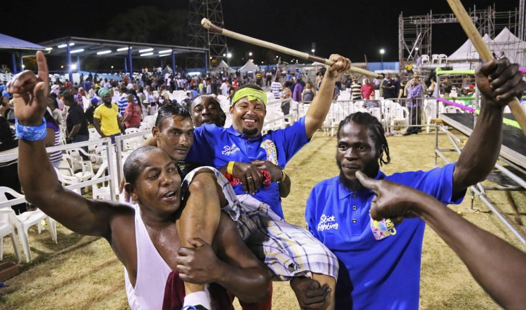 Stick fighter Learie Licorish, center, of the Campbell Trace gayelle, or stick fighting arena, is carried by teammates after he beat his rival to give Campbell Trace the victory in the finals of the national stick fighting competition, in San Fernando. (Andrea De Silva/Reuters photo)