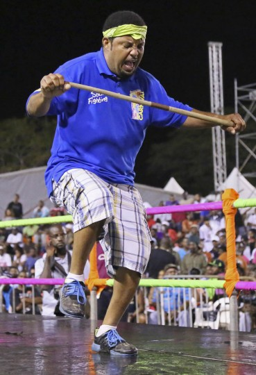 Stick fighter Learie Licorish, of the Campbell Trace gayelle, or stick fighting arena, does a dance before fighting a rival during the finals of the national stick fighting competition. (Andrea De Silva/Reuters photo)