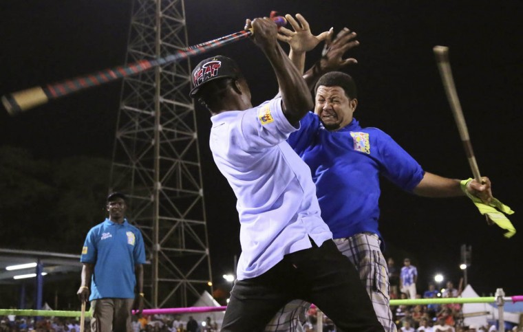 Stick fighter Learie Licorish, right, of the Campbell Trace gayelle, or stick fighting arena, fights rival Sean Lange of the Arouca gayelle during the finals of the national stick fighting competition, in San Fernando, February 19, 2014. (Andrea De Silva/Reuters photo)