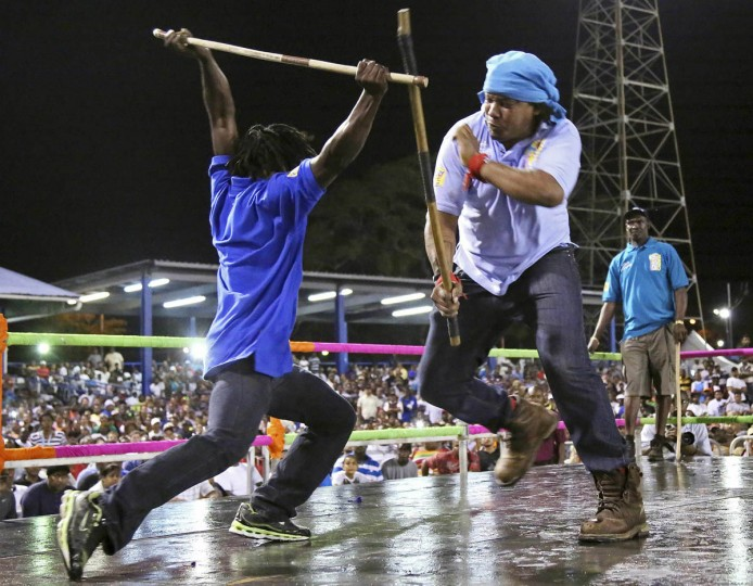 Stick fighter Anderson Marcano, left, of the Campbell Trace gayelle, or stick fighting arena, fights rival Evan Ralph of the Arouca gayelle during the finals of the national stick fighting competition. (Andrea De Silva/Reuters photo)