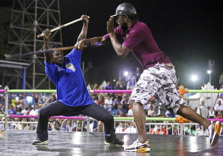 Stick fighter Anderson Marcano, left, of the Campbell Trace gayelle, or stick fighting arena, fights a rival from the Couva gayelle during the finals of the national stick fighting competition, in San Fernando, February 19, 2014. The stick fighting championship, which dates back to the days of slavery, is held every year at the beginning of Carnival season and the winner gets the title King of the Rock. Bouts are decided when a fighter draws blood from his opponent. (Andrea De Silva/Reuters photo)
