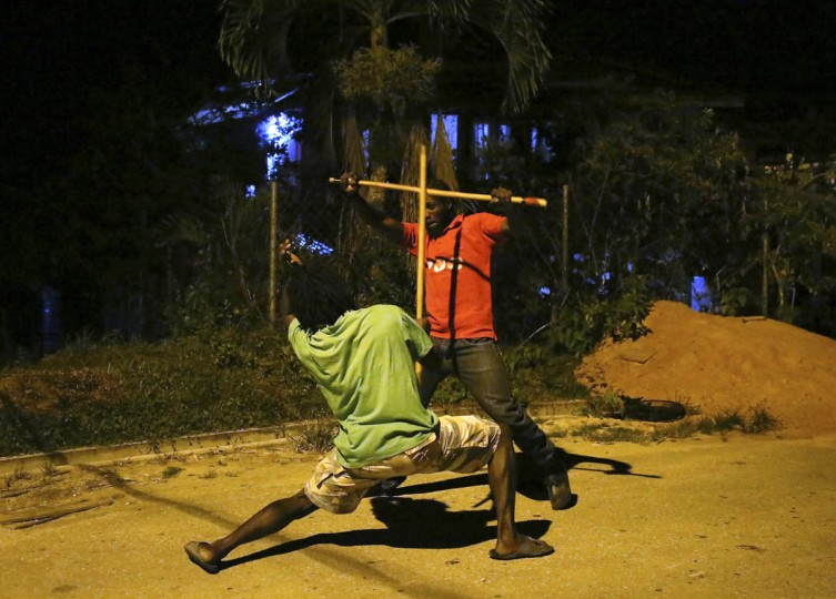 """Stick fighting brothers Andrew Marcano, left, former holder of the national """"King of the Rock"""" title, and his brother Terrance Marcano play fight as they prepare for the finals of the national stick fighting competition, in the village of Rio Claro, (Andrea De Silva/Reuters photo)"""