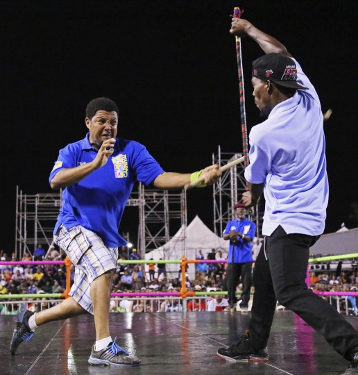"""Stick fighter Learie Licorish, left, of the Campbell Trace gayelle, or stick fighting arena, fights rival Sean Lange of the Arouca gayelle during the finals of the national stick fighting competition, in San Fernando, February 19, 2014. The stick fighting championship, which dates back to the days of slavery, is held every year at the beginning of Carnival season and the winner gets the title """"King of the Rock"""". Bouts are decided when a fighter draws blood from his opponent. (Andrea De Silva/Reuters photo)"""