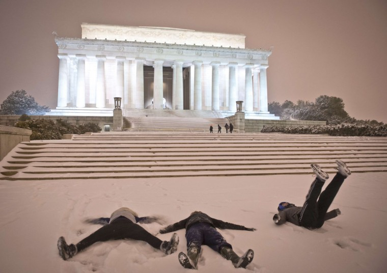 Young people make 'snow angel' in front of the Lincoln Memorial in Washington D.C. (MLADEN ANTONOV/AFP/Getty Images)