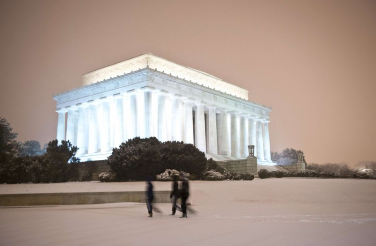 People walk in front of the Lincoln Memorial as a heavy snow storm hits Washington D.C. (MLADEN ANTONOV/AFP/Getty Images)