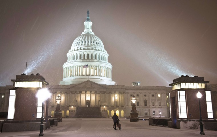 A cyclist looks at the US Congress building as a heavy snow storm hits Washington D.C. (MLADEN ANTONOV/AFP/Getty Images)
