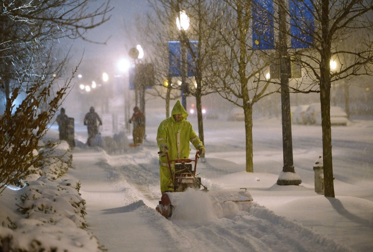 Workers use snow-blowers to clear snow from a sidewalk in Chevy Chase. (MANDEL NGAN/AFP/Getty Images)