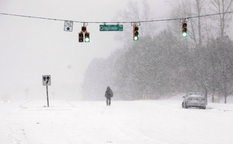 Turron Williams, who helped push cars stuck in the snow, crosses the intersection of Capanoke Road and Hammond Road in Raleigh, N.C. (Travis Long/Raleigh News & Observer/MCT)