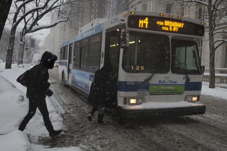 People board a bus on 5th Avenue at Central Park as it snows in New York. (REUTERS/Carlo Allegri)
