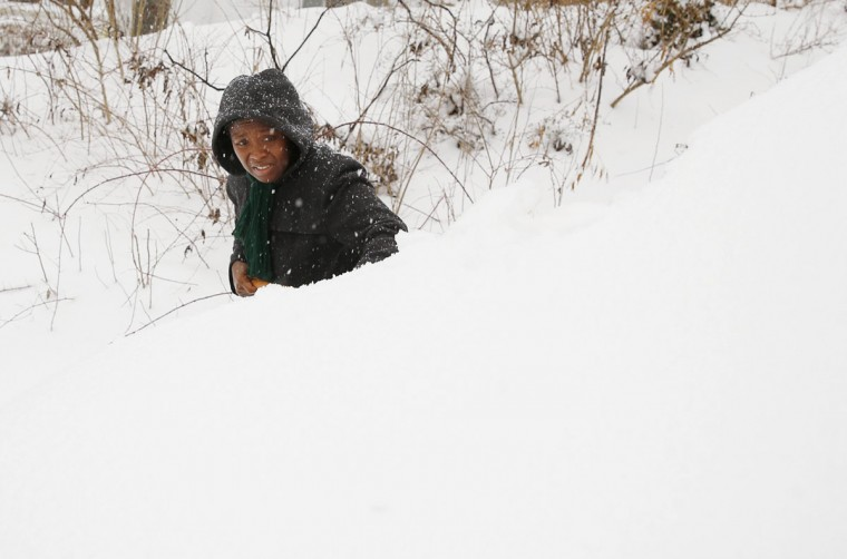 Oretha Bailey digs out her car that is buried in snow in Silver Spring. (REUTERS/Gary Cameron)