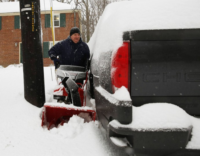 Tom Russell maneuvers his snow blower through a tight space in Silver Spring. (REUTERS/Gary Cameron)