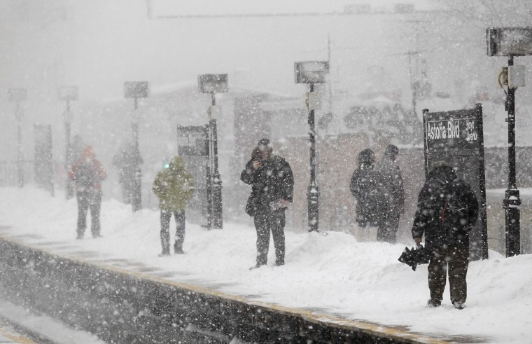 Commuters wait on the Metropolitan Transportation Authority platform for a train in heavy snow in the Queens borough of New York. (REUTERS/Joshua Lott)