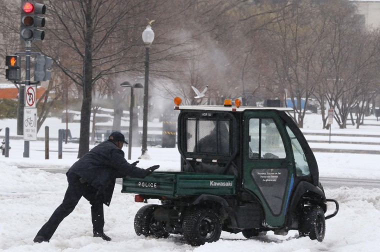 A guard from the U.S. National Gallery of Art pushes a police vehicle out after it got stuck in the snow during a major snow storm that closed U.S. Federal Government offices for the day and shut down much of the city of Washington. (REUTERS/Jim Bourg)