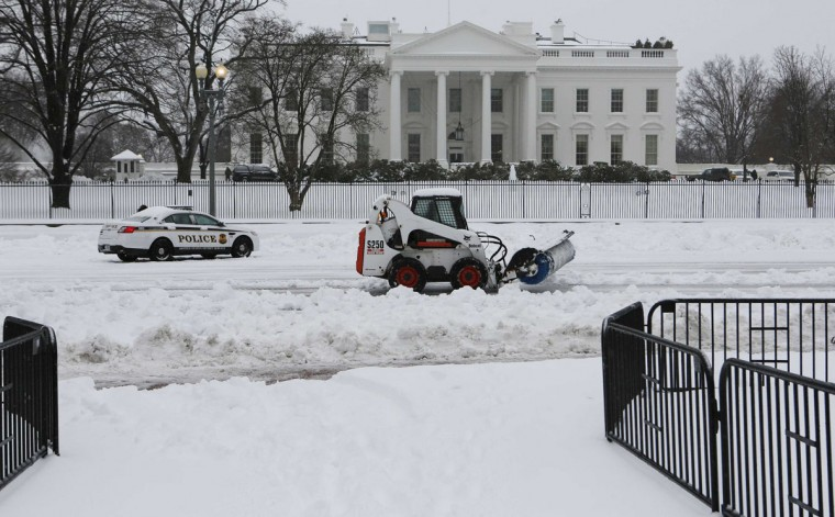 Snow removal equipment drives along Pennsylvania Ave.in front of the White House after the region was pounded with snow overnight around Washington. (REUTERS/Larry Downing)