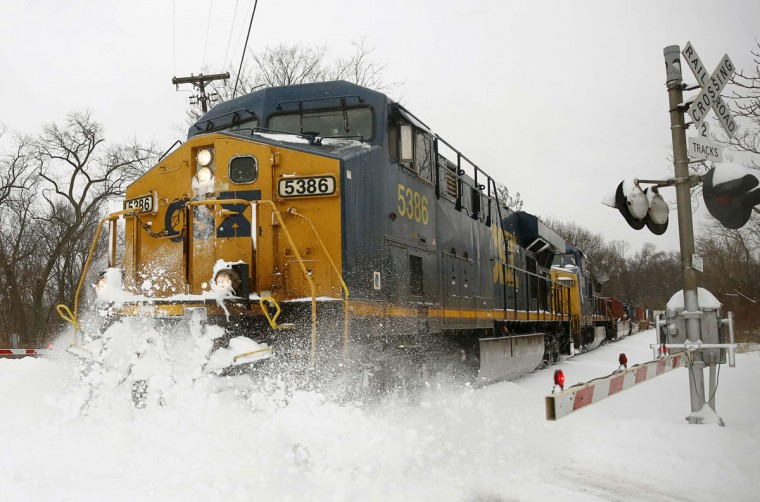 A CSX freight train blasts through high snow at a crossing in Silver Spring. (REUTERS/Gary Cameron)