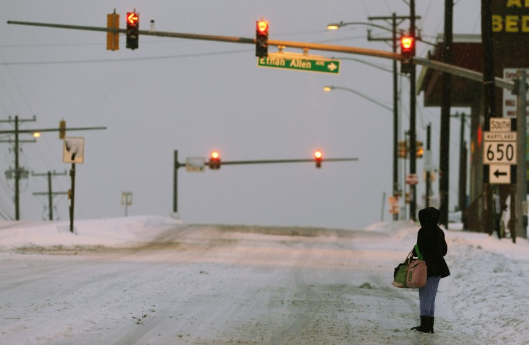A commuter waits for an early morning bus that is not going to arrive due to suspended bus service as a major snow storm hits the Washington area. (REUTERS/Jim Bourg)