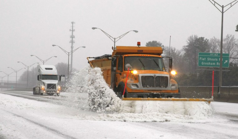 A snow plow knocks snow off an Atlanta expressway during an ice storm. (REUTERS/Tami Chappell)