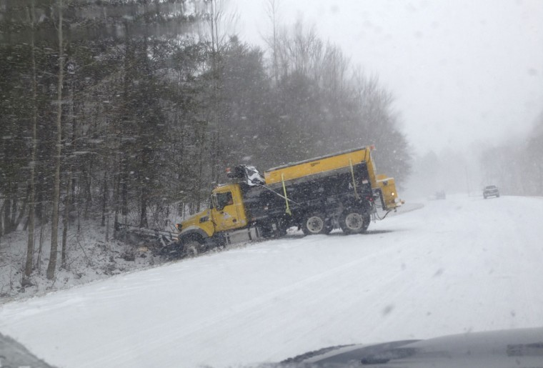 A snowplow finds itself in the ditch after sliding off a snow-covered North Carolina Highway. (REUTERS/Zach Albertson)