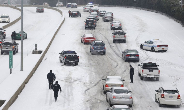 Charlotte Mecklenburg Police Officers work to assist motorists as they attempt to drive up a hill covered in snow in. (REUTERS/Chris Keane)