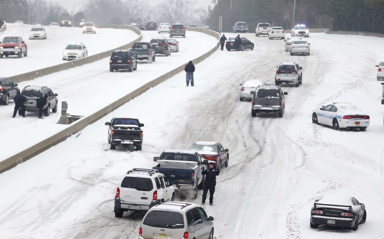 Charlotte Mecklenburg Police Officers work to assist motorists as they attempt to drive up a hill that is covered in snow. (REUTERS/Chris Keane )