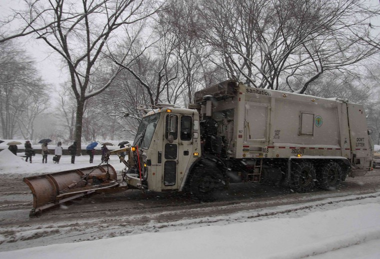 A garbage truck plows along 5th Avenue at Central Park as it snows in New York. (REUTERS/Carlo Allegri)